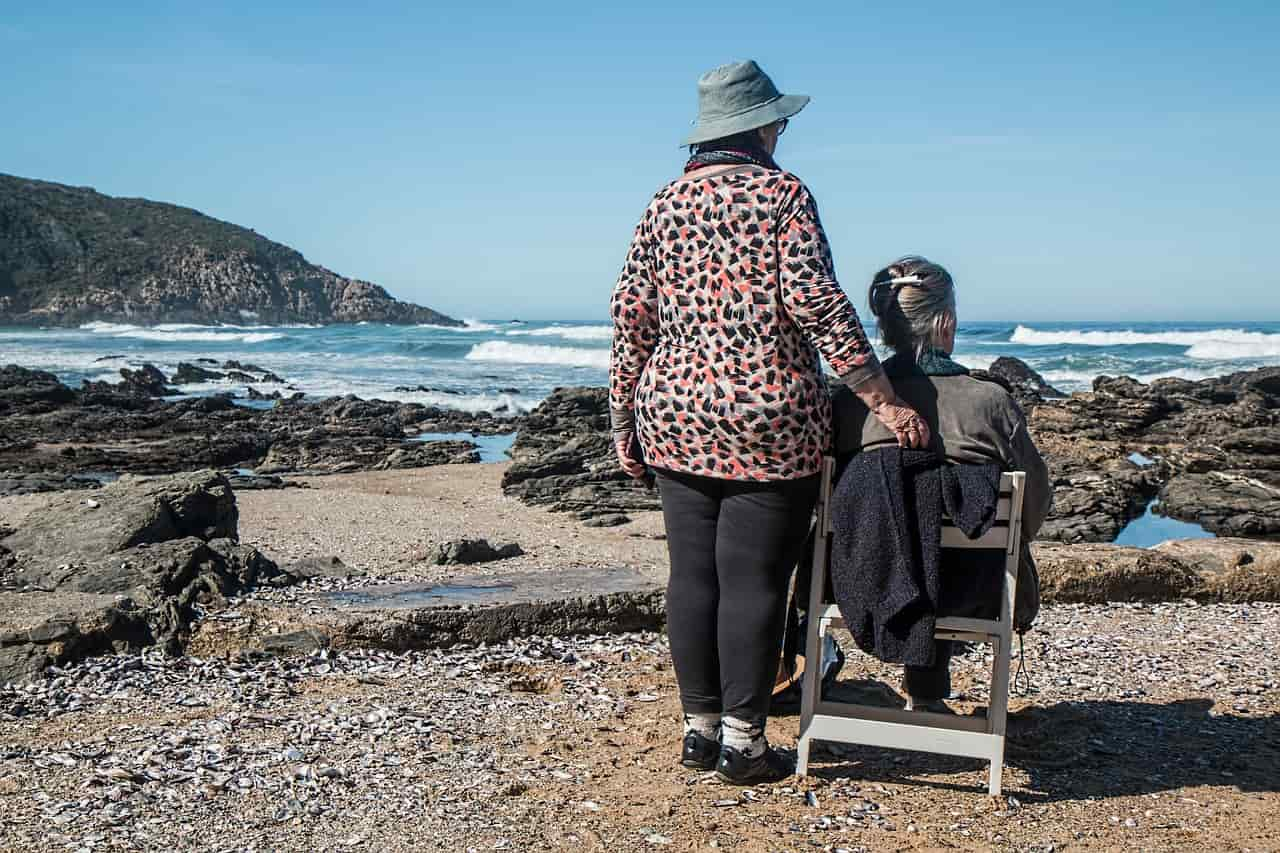 Woman standing next to another who is sitting in a chair by the seaside.